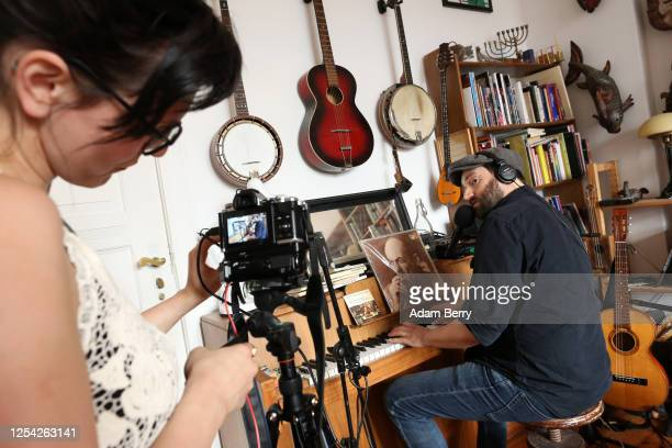 Musician Daniel Kahn plays piano as his wife and camera operator Yeva Lapsker livestreams his performance from their apartment as his contribution to...
