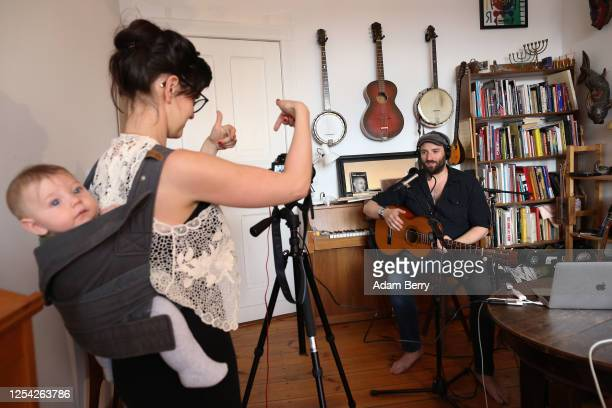 Musician Daniel Kahn plays the guitar and sings as his wife and camera operator Yeva Lapsker directs him as he livestreams his performance from their...