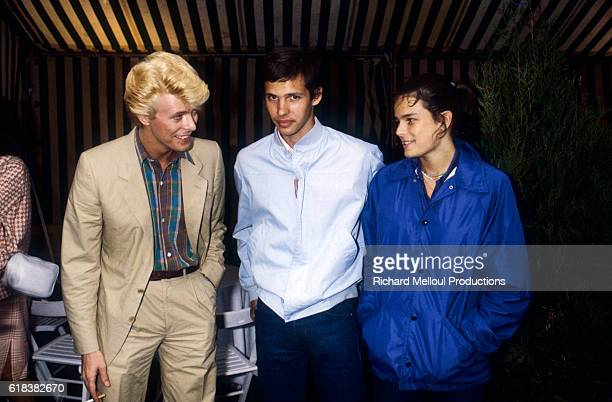 Musician David Bowie actor Paul Belmondo and Princess Stephanie of Monaco converse in Paris in June 1983