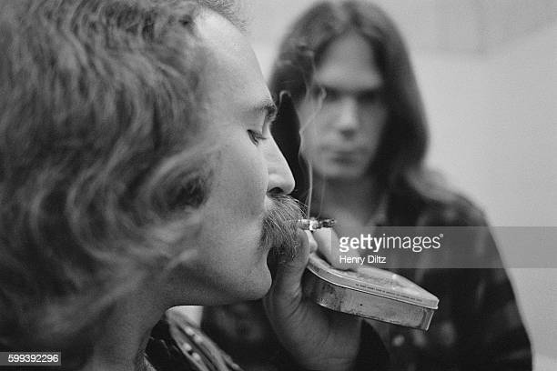 Musician David Crosby smokes a cigarette while Neil Young looks on They are in a backstage bathroom