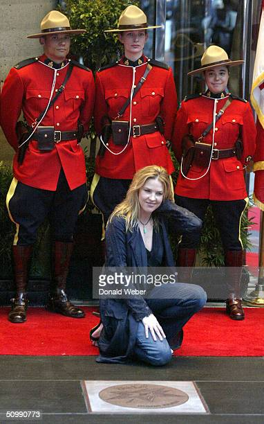 Musician Diana Krall kneels near her star after unveiling it on the Canadian Walk of Fame June 23 2004 in Toronto Canada