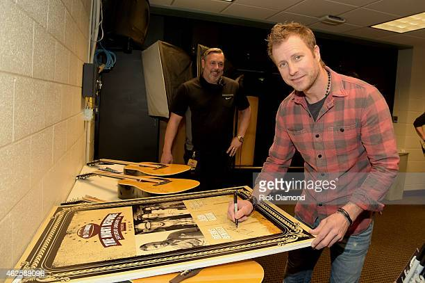 Musician Dierks Bentley signs autographs backstage during CBS Radio's The Night Before at US Airways Center on January 31 2015 in Phoenix Arizona