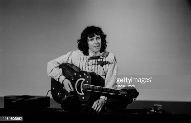 Musician Donovan sitting with crossed legs as he performs, April 1975.