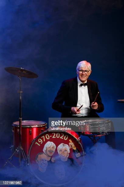 musician drummer active senior handsome man playing drum set. blue  background, with rays of light and special effects smoke. - modern rock stock pictures, royalty-free photos & images