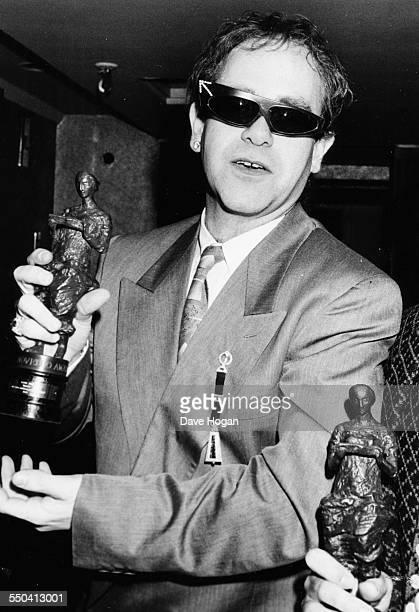 Musician Elton John holding an award at the Ivor Novello Awards London circa 1985