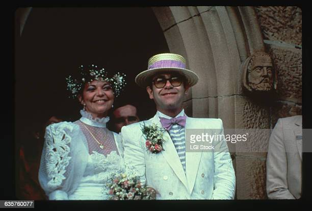 Musician Elton John leaves a church with his new bride Renate after their wedding