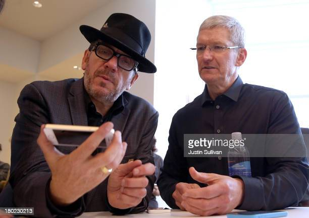 Musician Elvis Costello and Apple CEO Tim Cook look at the new iPhone 5S during an Apple product announcement at the Apple campus on September 10...