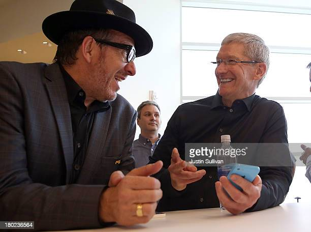 Musician Elvis Costello and Apple CEO Tim Cook look at the new iPhone 5C during an Apple product announcement at the Apple campus on September 10...