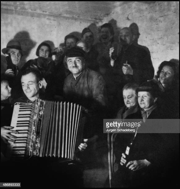 A musician entertains his companions on the accordion in an air raid shelter in Berlin during World War II 1942