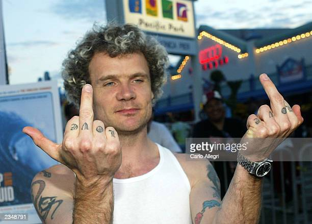 Musician Flea gives the fingers as he arrives for the premier of the movie Step Into Liquid on the Santa Monica Pier July 30 2003 on Santa Monica The...