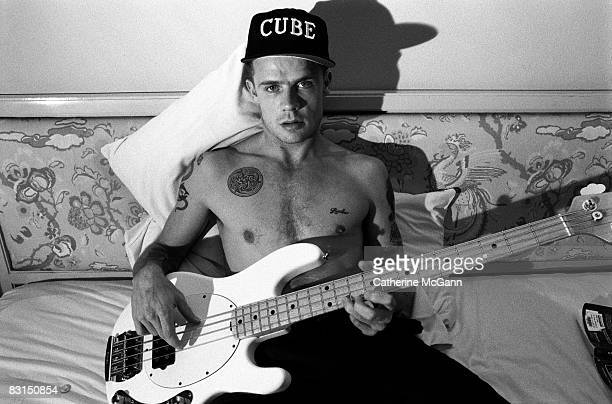 Musician Flea of the Red Hot Chili Peppers poses shirtless in his hotel room for a portrait while holding his guitar and wearing a baseball cap which...