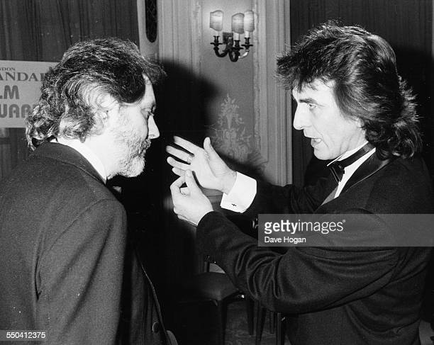 Musician George Harrison talking to film producer David Puttnam at the Evening Standard Film Awards London January 28th 1986