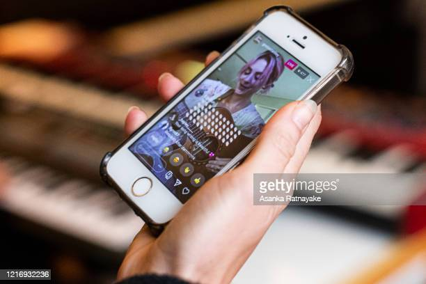 Musician Greta Stanley performance is viewed via a live streamed seen on a phone as part of IsolAid on April 05 2020 in Melbourne Australia The...