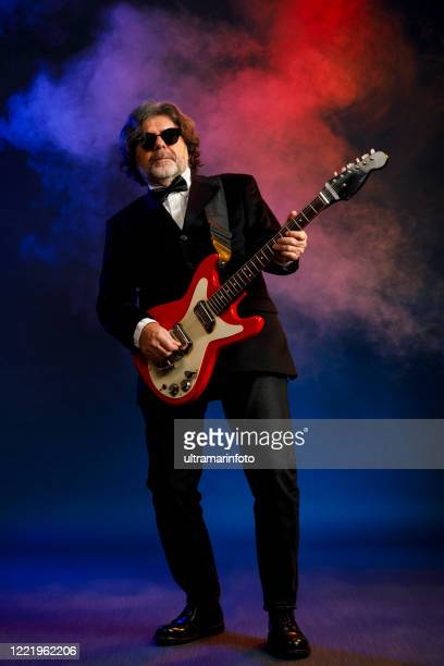 musician guitarist active senior handsome man playing guitar. blue  background, with rays of light and special effects smoke. - modern rock stock pictures, royalty-free photos & images