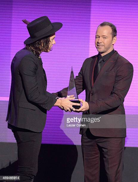 Musician Harry Styles of One Direction and actor Donnie Wahlberg speak onstage at the 2014 American Music Awards at Nokia Theatre LA Live on November...