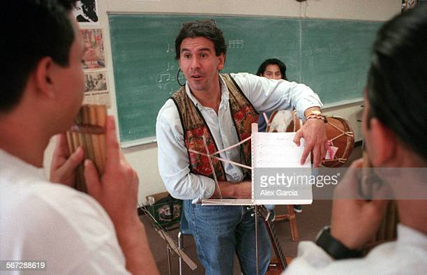 Musician Hernan Pinilla helps students in his Saturday music class at Valley High School in Santa Ana in which he teaches Andean music played with...