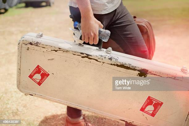 musician holding his guitar case - guitar case stock pictures, royalty-free photos & images