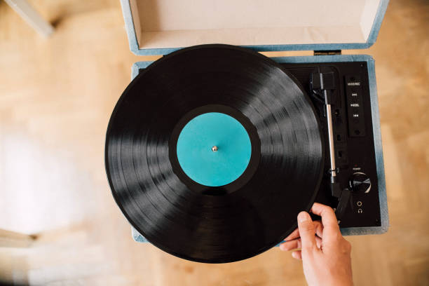 Musician holding record on turntable at home