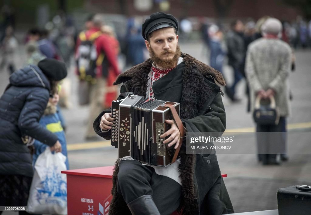 A musician in a traditional Russian costume plays the accordion in
