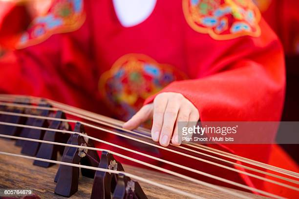 Musician in Korean traditional outfit playing Gayageum