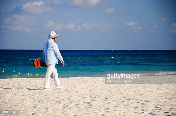 CONTENT] A musician is walking on the beach holding a little guitar in Playa del Carmen Quintana Roo Mexico The man is wearing a white hat and white...