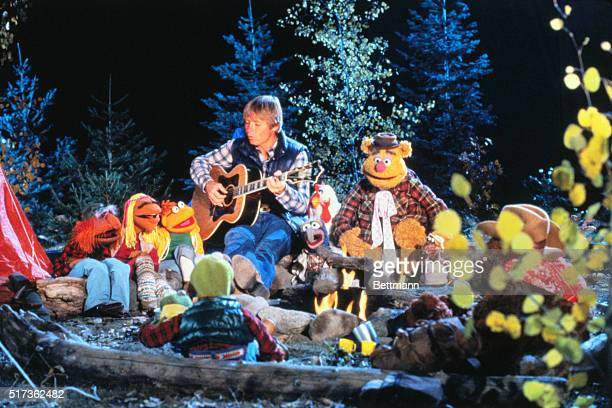 Musician John Denver during an appearance on the Muppet Show He is seated around a campfire with Kermit the Frog unidentified Janis Scooter John...