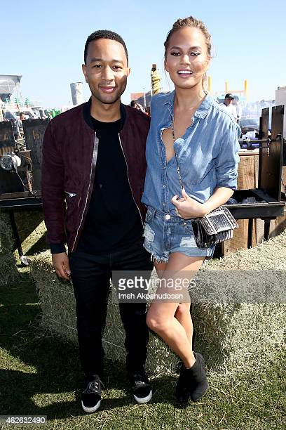 Musician John Legend and model Chrissy Teigen attend the DIRECTV Super Fan Tailgate at Pendergast Family Farm on February 1 2015 in Glendale Arizona