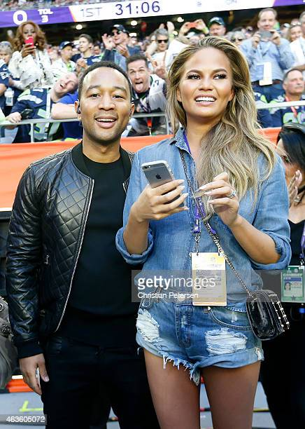 Musician John Legend and model Chrissy Teigen look on during Super Bowl XLIX between the Seattle Seahawks and the New England Patriots at University...