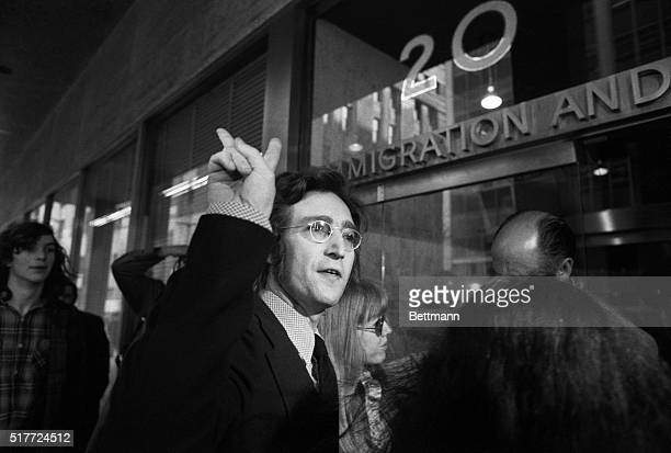 Musician John Lennon flashes a peace sign as he and Yoko Ono appear at the New York office of Immigration and Naturalization in May of 1972 to fight...