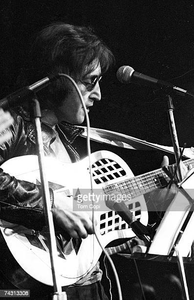 """Musician John Lennon formerly of """"The Beatles"""" performs onstage at the Chrysler Arena on December 10, 1971 in Ann Arbor, Michigan."""