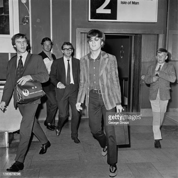 Musician John Lennon of the Beatles leaves London Airport for Hanover in Germany, 5th September 1966. Second from the left, in the background, is...