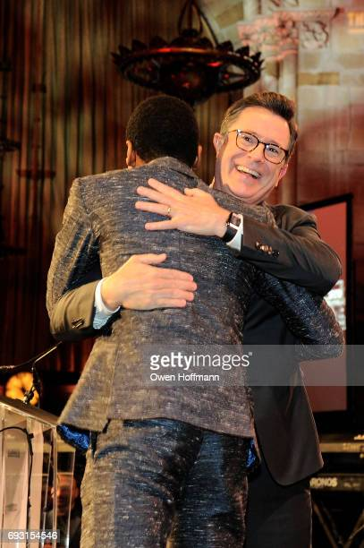 Musician Jon Batiste and comedian Stephen Colbert embrace onstage during the Gordon Parks Foundation Awards Dinner Auction at Cipriani 42nd Street on...