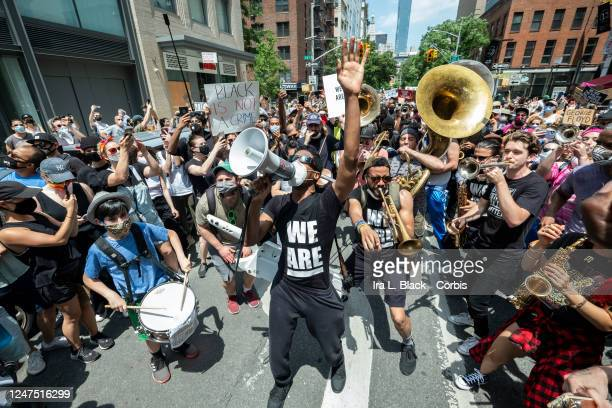 Musician Jon Batiste holds up his hands while his band jams for the crowd of people that have followed him onto to 6th Avenue from Union Square for a...