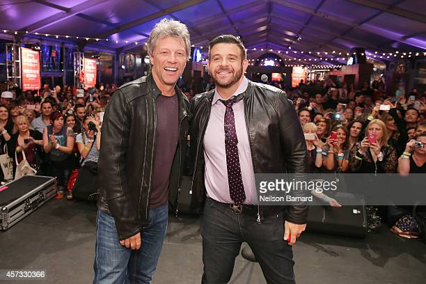 Musician Jon Bon Jovi and TV personality Adam Richman pose on stage at Ronzoni's La Sagra Slices hosted by Bongiovi Brand pasta sauces Adam Richman...
