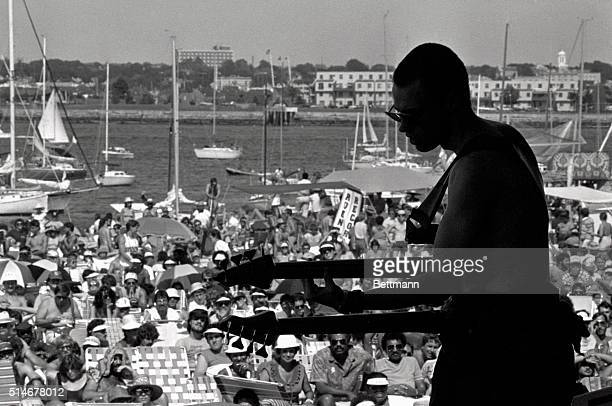 Musician Jonas Hellborg performs with the Mahavishnu Orchestra at the Newport Jazz Festival. A crowd relaxes in the sun along the harbor in Fort...