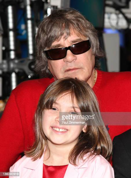 Musician Jose Feliciano and MakeAWish Child Katherine Mara pose after ringing the closing bell at the New York Stock Exchange on December 23 2011 in...