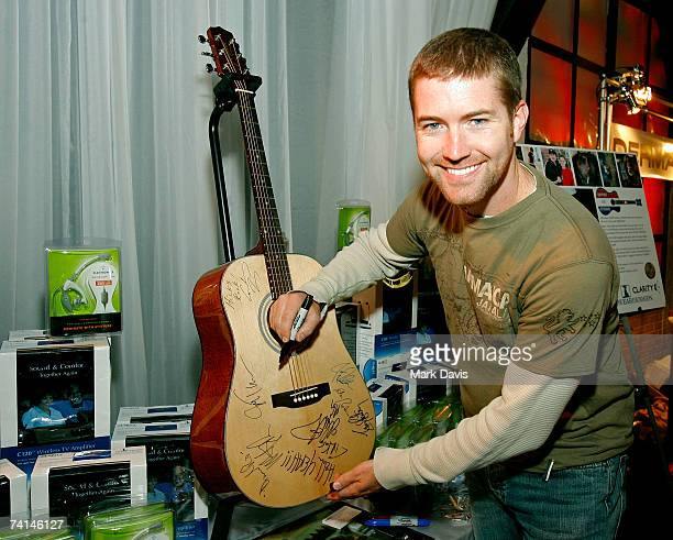 Musician Josh Turner autographs a guitar at the Ear Foundation/Clarity display in the Distinctive Assets gift lounge during the Academy of Country...