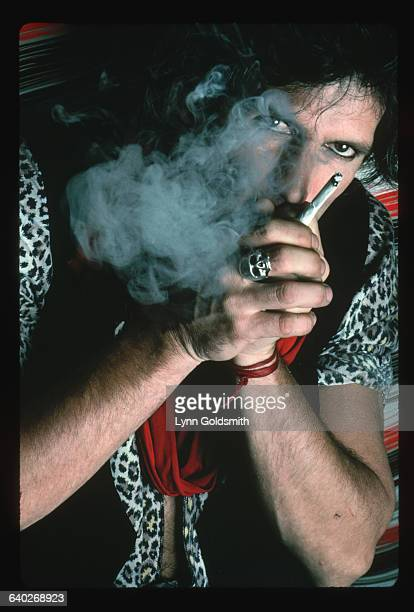 Musician Keith Richards guitarist for the British rock roll band The Rolling Stones hides behind a cloud of cigarette smoke in this closeup portrait...