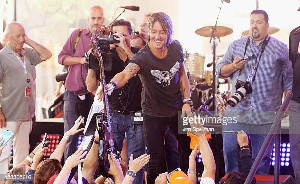 Musician Keith Urban gives a fan his guitar during his performance on NBC's Today at Rockefeller Plaza on August 7 2015 in New York City