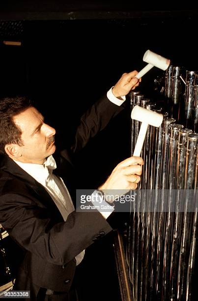 Musician Kevin Hathaway plays a set of tubular bells using mallets while wearing evening dress circa 1998