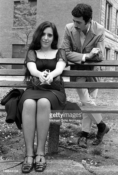Musician Laura Nyro sits on a park bench as music executive David Geffen looks on during a portrait session in 1969 in New York New York