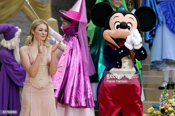 Musician Leann Rimes and Mickey Mouse stand in front of the Sleeping Beauty Castle after launching the Happist Celebration on Earth during the...