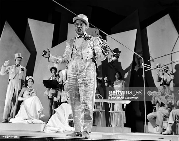 Musician Louis Armstrong holds his trumpet as he performs in a scene from the movie 'Dr Rhythm' which was released in 1938