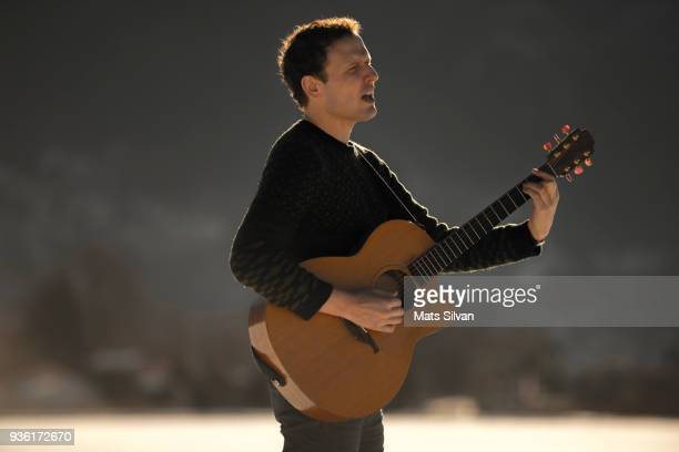 Musician Man Playing and Singing with his Guitar with Sunlight