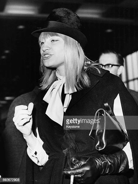 Musician Mary Travers of the folk band 'Peter Paul and Mary' smoking a cigarette as she arrives at London Airport April 3rd 1964