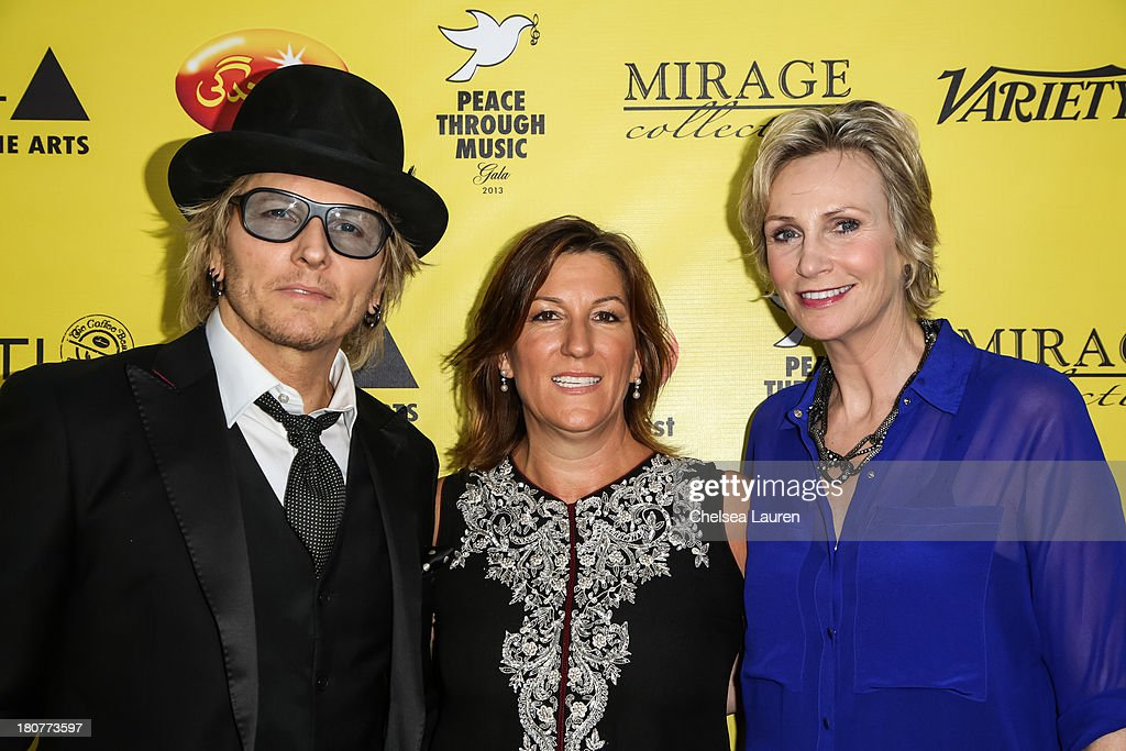 Musician Matt Sorum, Abigail Berman and actress Jane Lynch arrive at Adopt the Arts' Peace Through Music celebrity gala at Loews Hollywood Hotel on September 15, 2013 in Hollywood, California.