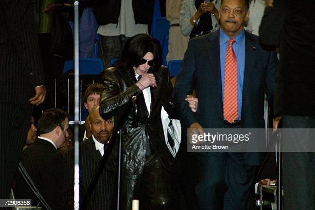 Musician Michael Jackson and the Reverend Jesse Jackson approach the stage during a homegoing celebration for musician James Brown at the James Brown...