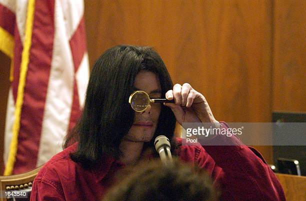 Musician Michael Jackson looks though a magnifying glass during his civil trial in Santa Maria Superior Court November 14 2002 in Santa Maria...