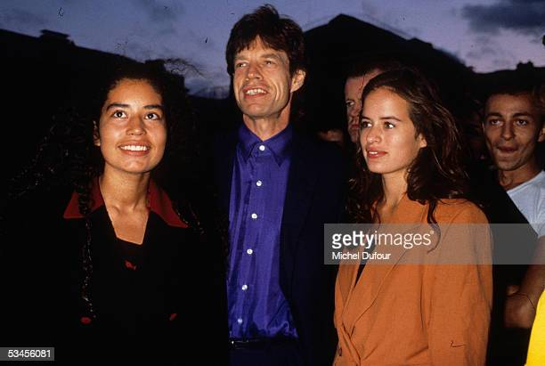 Musician Mick Jagger of The Rolling Stones poses with his daughters Karis and Jade in 1995 in Paris France