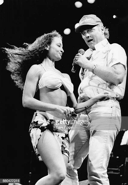Musician Mike Love with the band 'The Beach Boys' performing on stage as a dancer in a bathing suits walks past at the NEC Arena in Birmingham...
